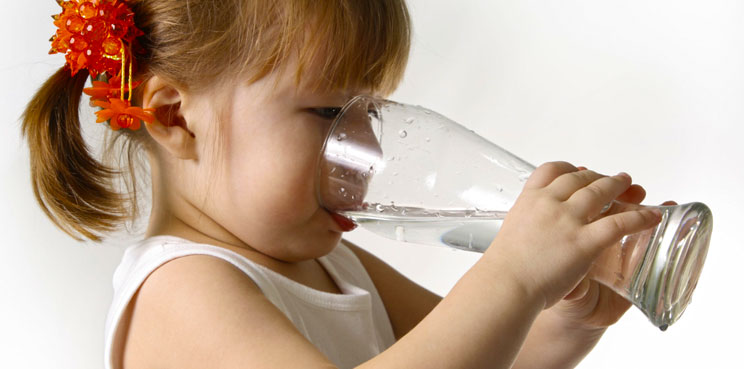 child girl drinking clean water from large glass