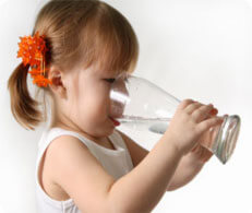child girl drinking water out of large glass