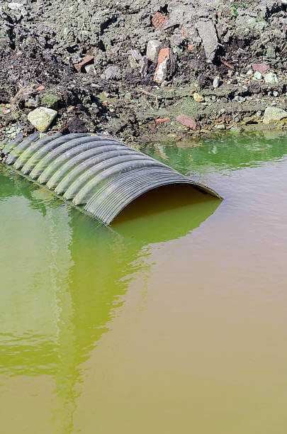 toxic green yellow water with half submerged exit pipe sewage and chemical drain