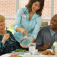 assisted living woman pouring clean water for elderly at table