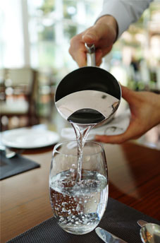 pouring water into pitcher at restaurant