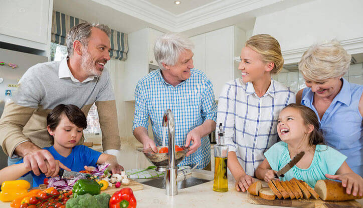 smiling family different woman man kids parents generations around kitchen table sink preparing vegetables and cutting bread making dinner olive oil
