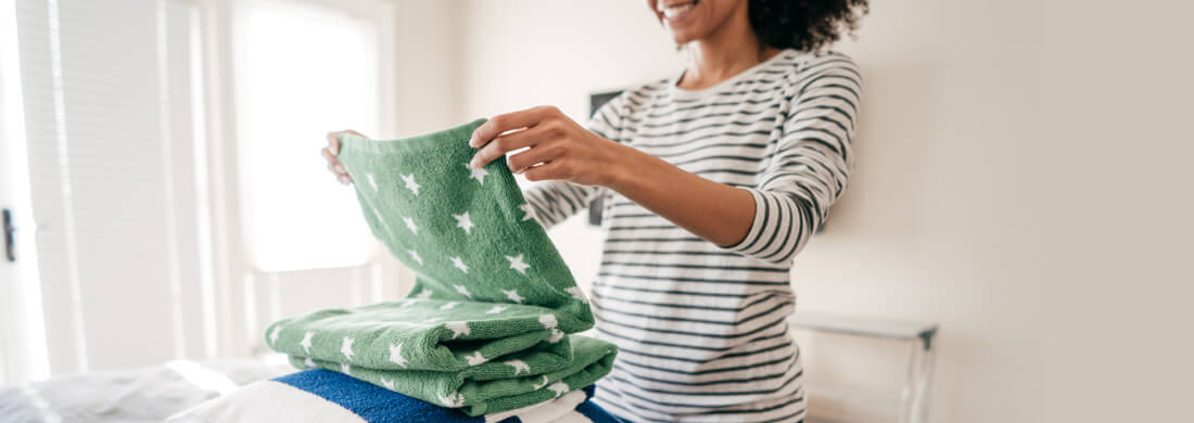 woman in striped shirt folding green and blue towels after wash in laundry room