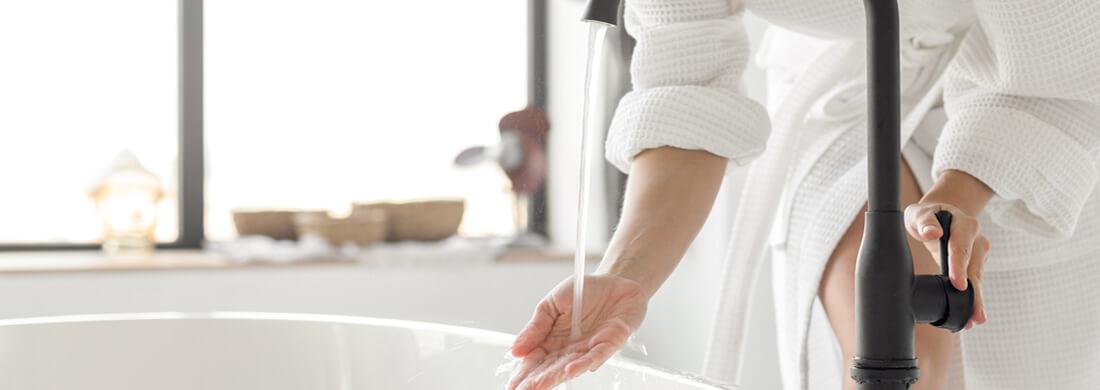 woman putting hand under faucet bath bathroom white robe particulate platinum series